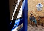 A man sits outside of Asilah's Arabic calligraphy shop