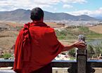 Monk looking out at the view over Songzanlin Monastery in Zhongdian