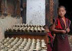 Boy monk next to butterlamps, Jakar