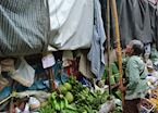 Lady putting up her stall in a market on the railway tracks in Amphawa