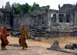 Buddhist monks walk alongside the central sanctuary at Preah Vihear