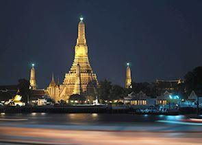 Wat Arun shines brightly alongside the Chao Praya River, Bangkok, Thailand