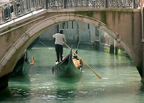 Gondola under old bridge, Venice