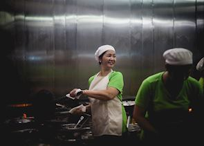 Woman cooking in an open kitchen in downtown Saigon
