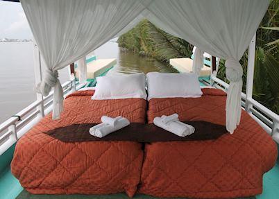 Upper deck double bed on Deluxe Klotok Boat