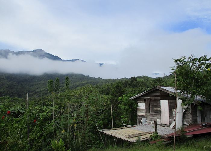 A village house in Kampong Nyegol with mist rising over the mountains