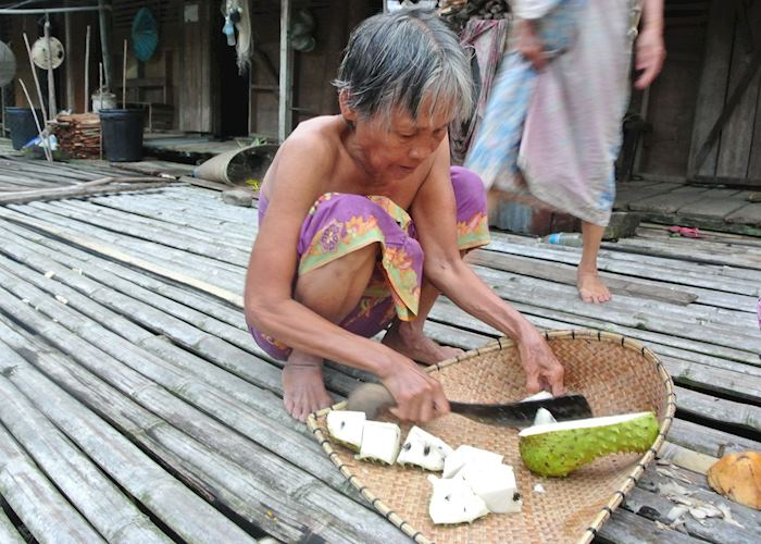 Lady preparing fruit at the Lemanak Longhouse