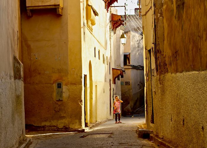 A little girl gazes down the cobbled streets of the ancient medina in Fez.