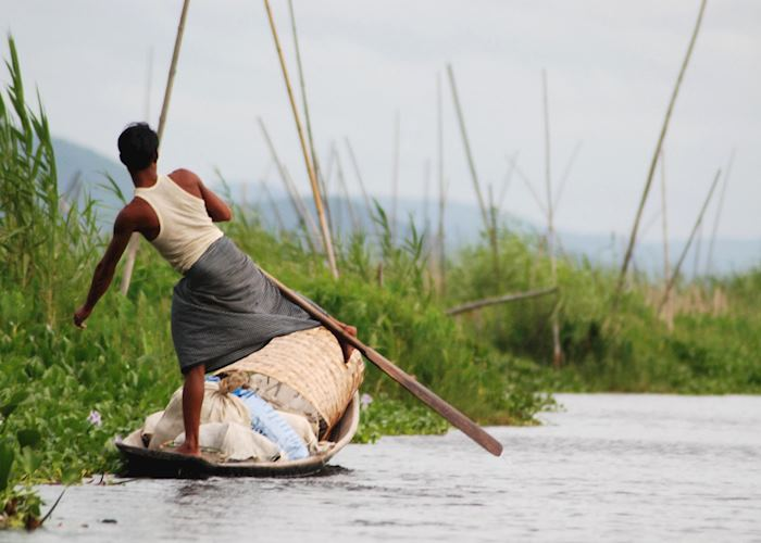 A leg rower transports his goods on one of the channels to Inle Lake