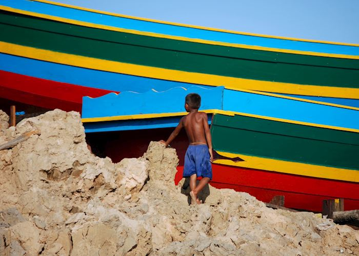 Young boy exploring the freshly painted boats - Tonle Sap