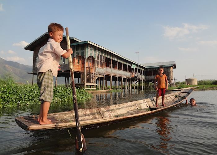 Kids attempting the one-legged rowing technique on Inle Lake