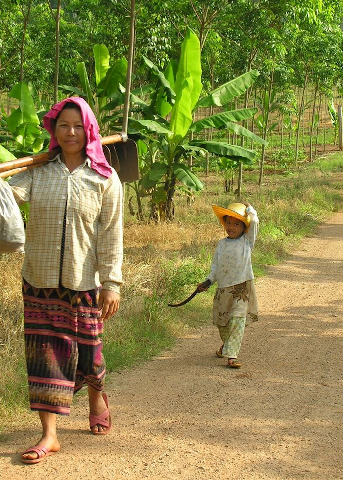 A woman and her daughter return from tending their crops