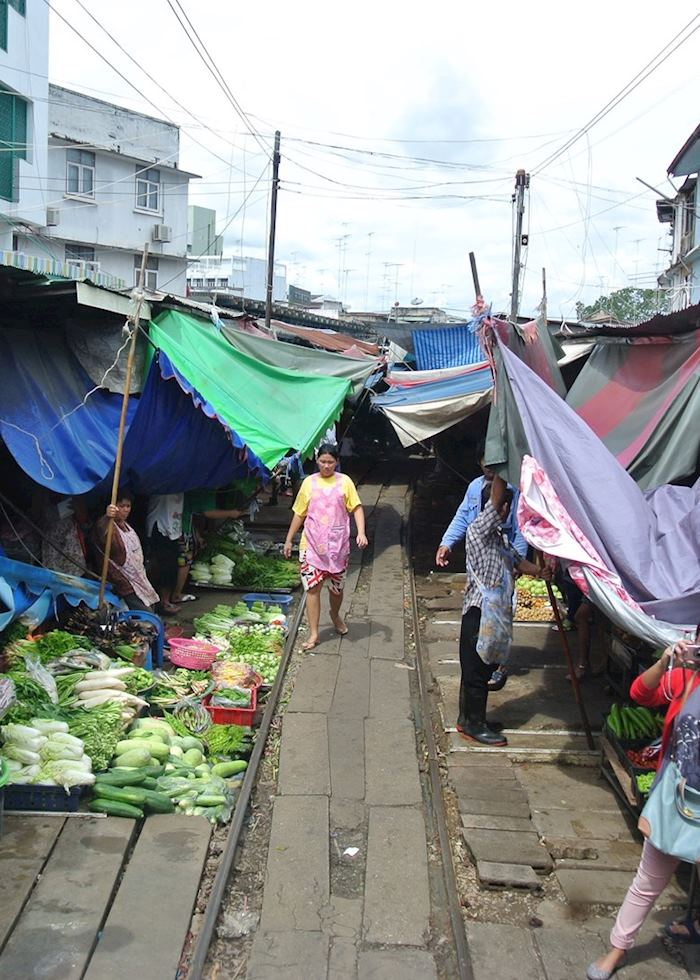 The art of reassembling market stalls on the railway track in Amphawa